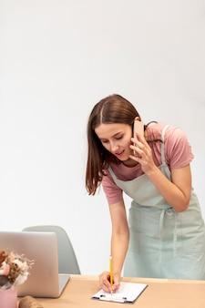 Bedrijfsvrouw die op telefoon spreken en nota's nemen