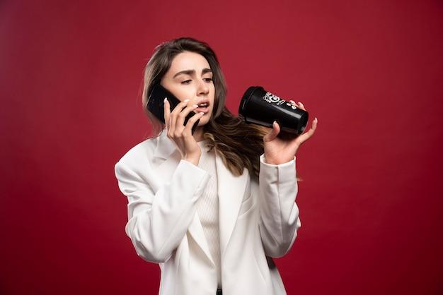 Bedrijfsvrouw die op telefoon spreken en op een koffiekop kijken
