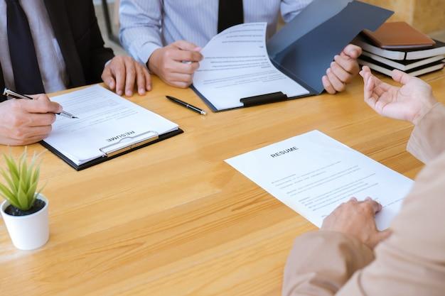 Bedrijfsvrouw die over zijn profiel aan commissiemanager verklaren die tijdens tijdens baangesprek zitten