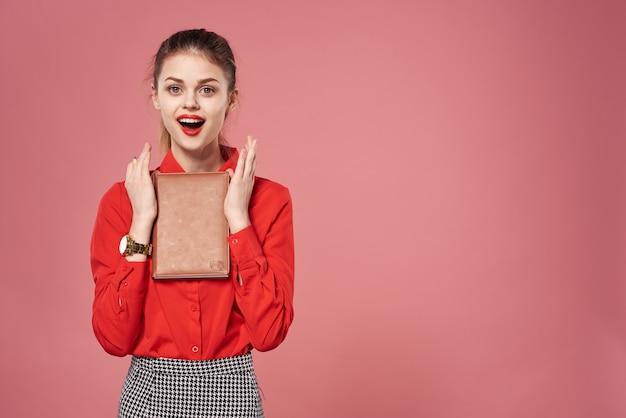Bedrijfsvrouw die rood overhemd draagt dat een notebloc houdt