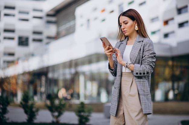 Bedrijfsvrouw die telefoon buiten in de straat gebruiken door het gebouw