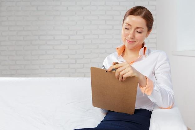 Bedrijfsvrouw die thuis bureau voor planning en het schrijven op een notitieboekje werken
