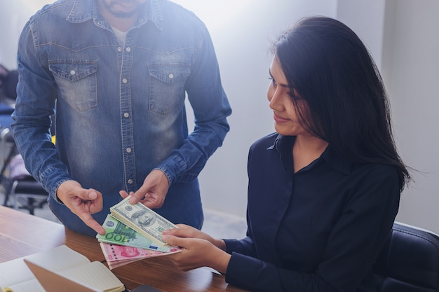 Bedrijfsvrouw die usd dollars, yuan rmb, euro geld houden