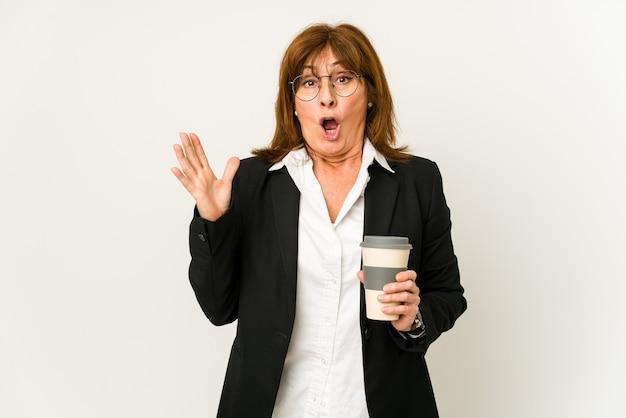 Bedrijfsvrouw die van middelbare leeftijd een afhaalkoffie houden, verrast en geschokt.