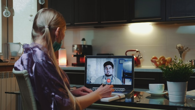 Bedrijfsvrouw die videogesprek voeren met een arts en medisch overleg van huis krijgen