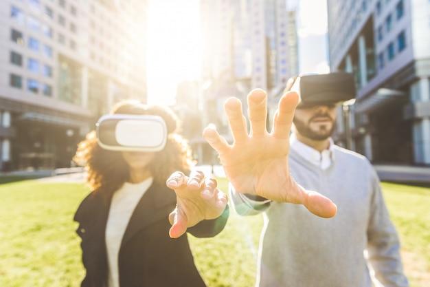 Bedrijfsvrouw en man die virtuele werkelijkheidshoofdtelefoon dragen