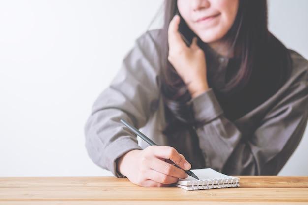 Bedrijfsvrouw gebruikend telefoon en schrijvend notitieboekje