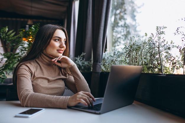 Bedrijfsvrouw het drinken koffie en het werken aan laptop in een koffie