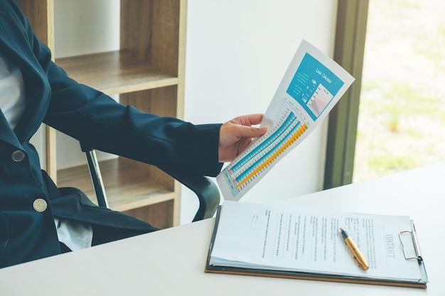 Bedrijfsvrouw het werken en analysedocument van leningscalculator