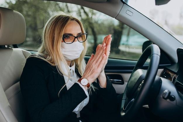 Bedrijfsvrouw in de zitting van het beschermingsmasker in een auto die antiseptisch gebruiken