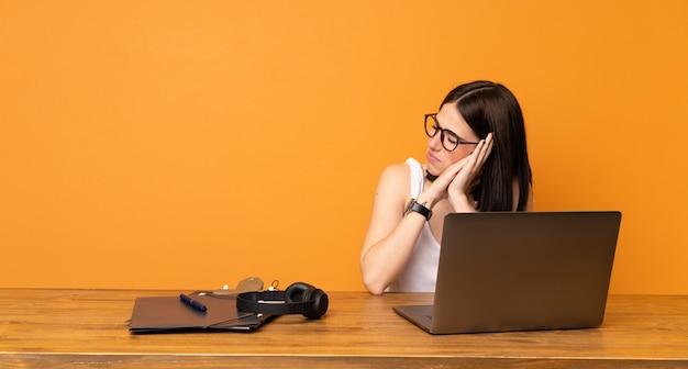 Bedrijfsvrouw in een bureau dat slaapgebaar in aanbiddelijke uitdrukking maakt