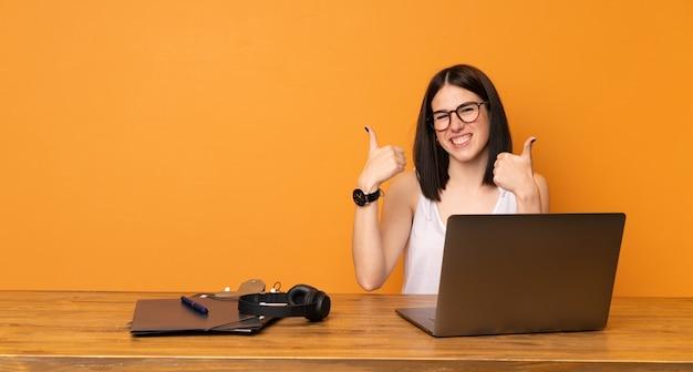 Bedrijfsvrouw in een bureau met duimen op gebaar en het glimlachen