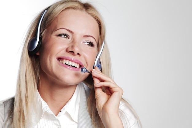 Bedrijfsvrouw in een hoofdtelefoon op een grijze muur