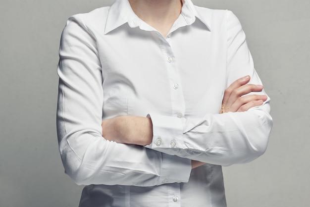 Bedrijfsvrouw in een witte blouse met gekruiste wapens