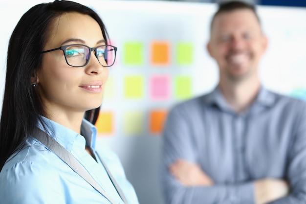 Bedrijfsvrouw in glazen op achtergrond van de glimlachende mens