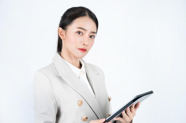 Bedrijfsvrouw in grijs kostuum die tablet en pen gebruiken om de notulen van vergadering en het werk te registreren.