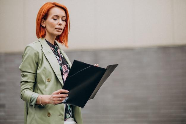 Bedrijfsvrouw in groen kostuum die zich met omslag bevinden