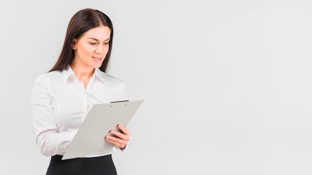 Bedrijfsvrouw in overhemd die op klembord schrijven