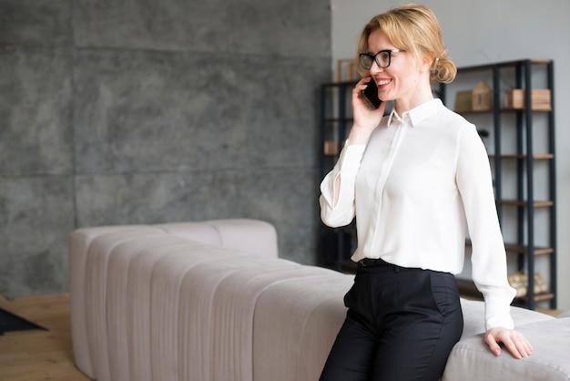 Bedrijfsvrouw in wit overhemd die op telefoon spreken