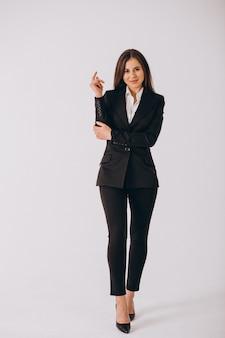 Bedrijfsvrouw in zwart kostuum dat op witte achtergrond wordt geïsoleerd