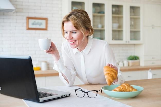 Bedrijfsvrouw met croissant die laptop met behulp van