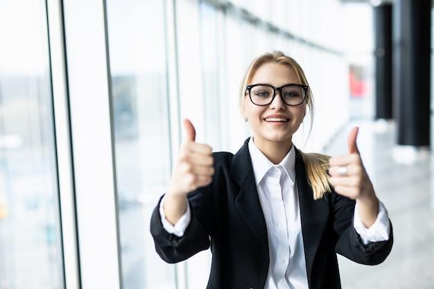 Bedrijfsvrouw met duimen omhoog in bureau met panoramische vensters