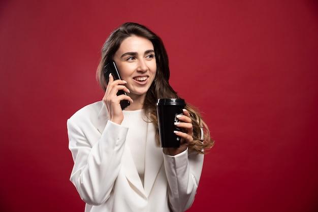 Bedrijfsvrouw met een koffiekop die op telefoon spreekt