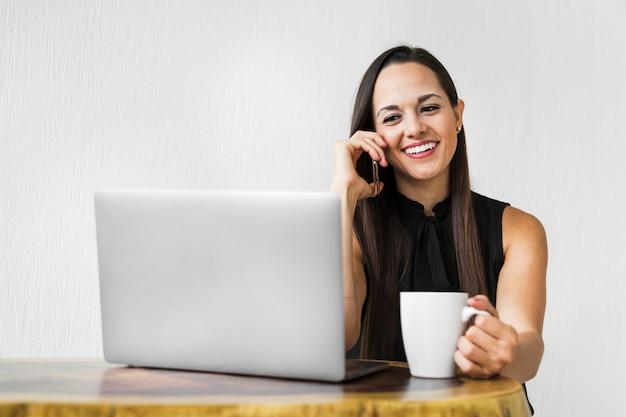 Bedrijfsvrouw met een kop van koffie die bij de telefoon spreekt