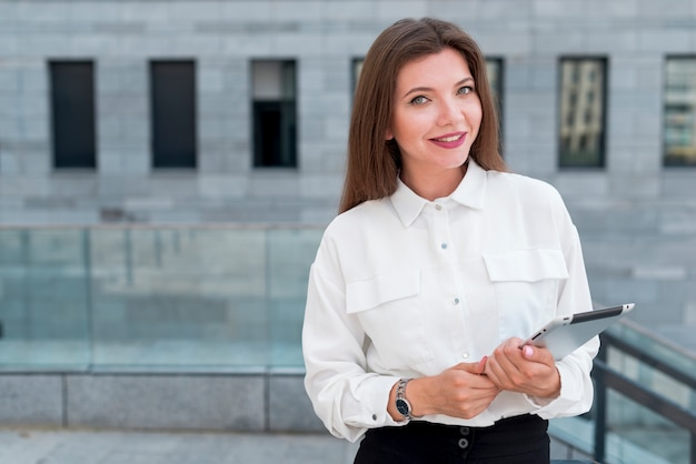 Bedrijfsvrouw met een tablet in de straat