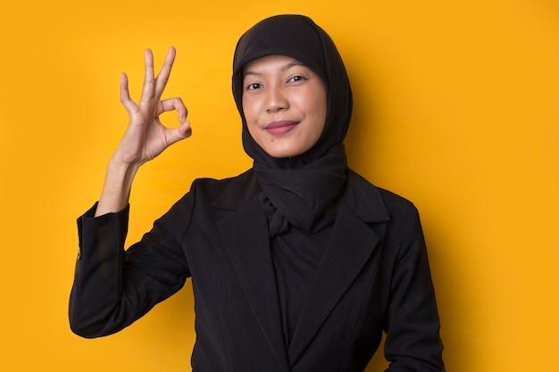 Bedrijfsvrouw met hijabportret dat ok gebaar toont