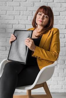 Bedrijfsvrouw met klembord op stoel