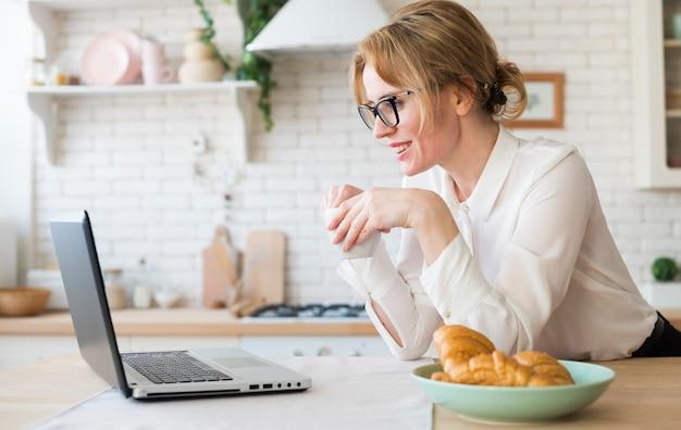 Bedrijfsvrouw met koffie die laptop met behulp van