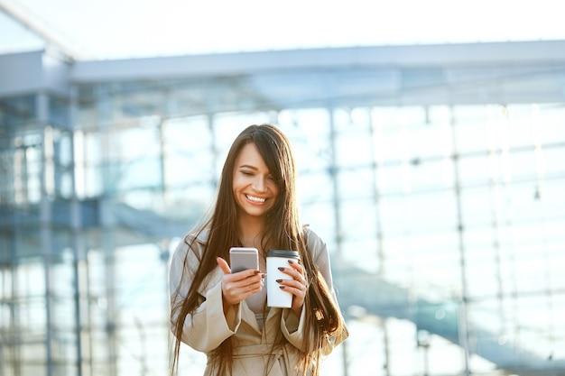 Bedrijfsvrouw met koffie en de telefoon dichtbij bureau. portret van mooie glimlachende vrouw met telefoon, buitenshuis staan. telefonische communicatie.