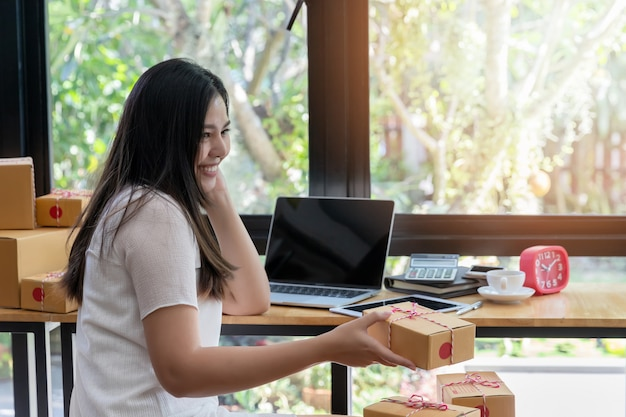 Bedrijfsvrouw met online verkoop en pakketverzending in haar thuiskantoor.