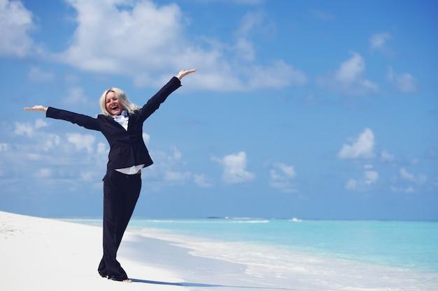 Bedrijfsvrouw met opgeheven handen op oceaanstrand