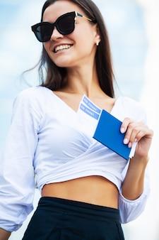 Bedrijfsvrouw met paspoort en kaartjes dichtbij luchthaven