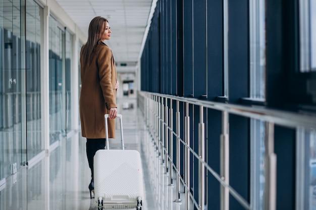 Bedrijfsvrouw met reiszak in luchthaven