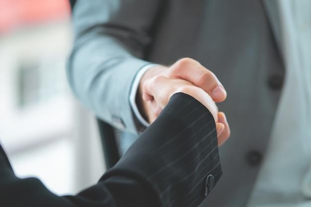 Bedrijfsvrouw met vertrouwenshanddruk met partner