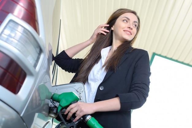 Bedrijfsvrouw op benzinestation, terwijl het vullen van uw auto.