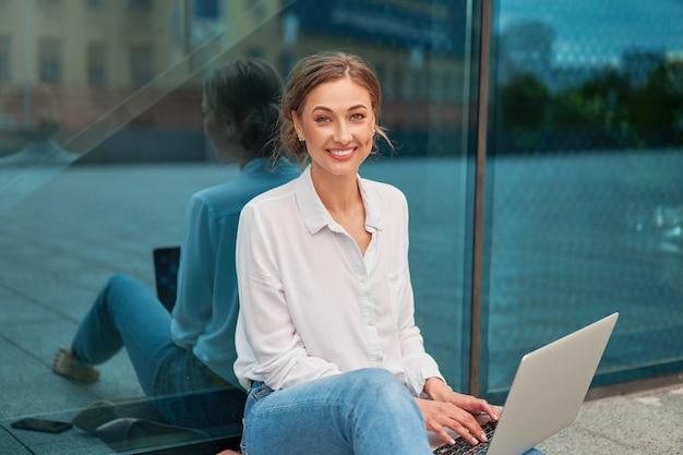 Bedrijfsvrouw succesvolle vrouw bedrijfspersoon openlucht met cellaptop