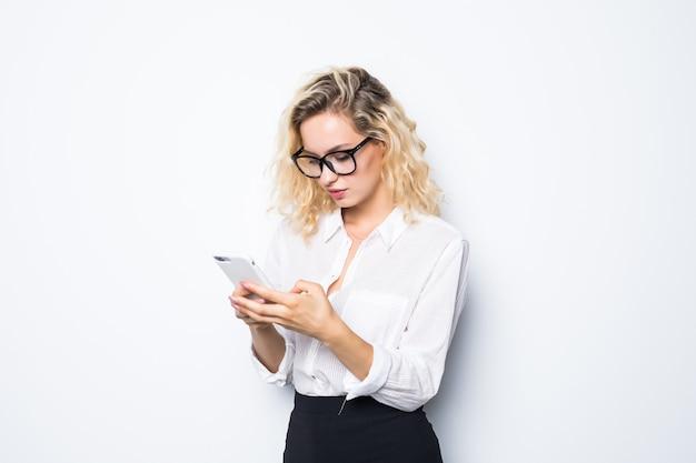 Bedrijfsvrouw texting op haar mobiele telefoon die over witte muur wordt geïsoleerd
