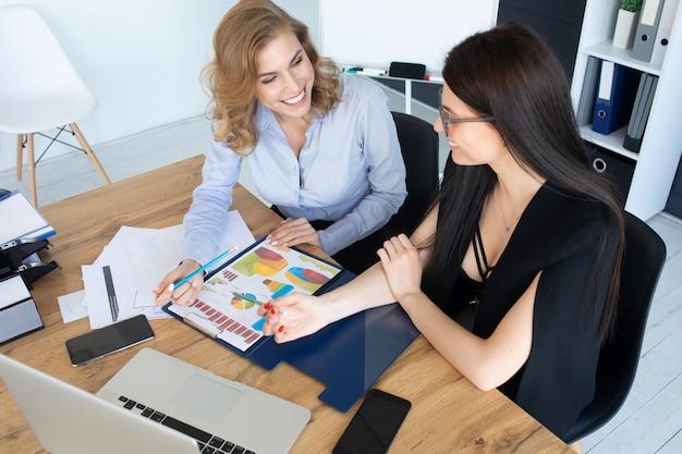 Bedrijfsvrouwen die bij bureau aan laptop, groepswerkconcept samenwerken