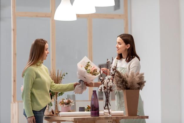 Bedrijfsvrouwen die bij de zitting van de bloemwinkel zijdelings werken