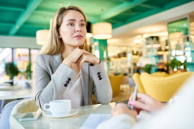 Bedrijfsvrouwen die bij koffiepauze samenkomen
