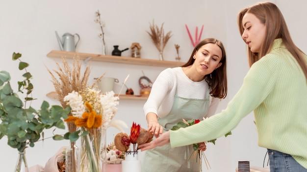 Bedrijfsvrouwen die de bloemen schikken