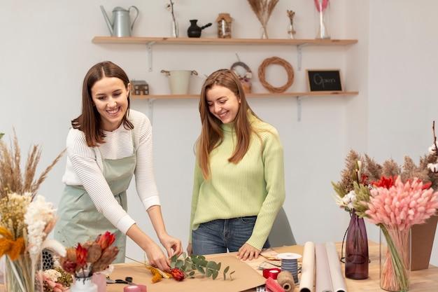 Bedrijfsvrouwen die de bloemenwinkel schikken