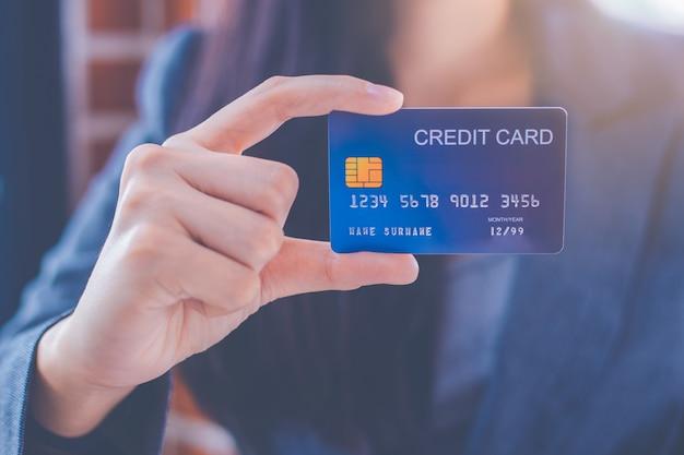 Bedrijfsvrouwen die een blauwe creditcard tonen