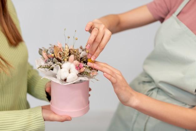 Bedrijfsvrouwen die een boeket van bloemen maken