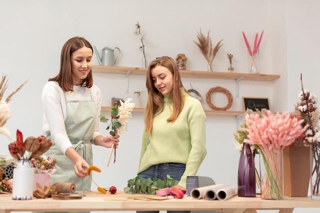 Bedrijfsvrouwen die een boeket van bloemen schikken