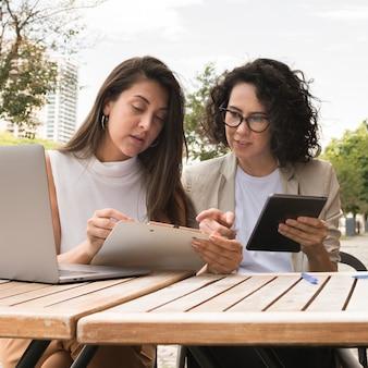 Bedrijfsvrouwen die in openlucht samenwerken